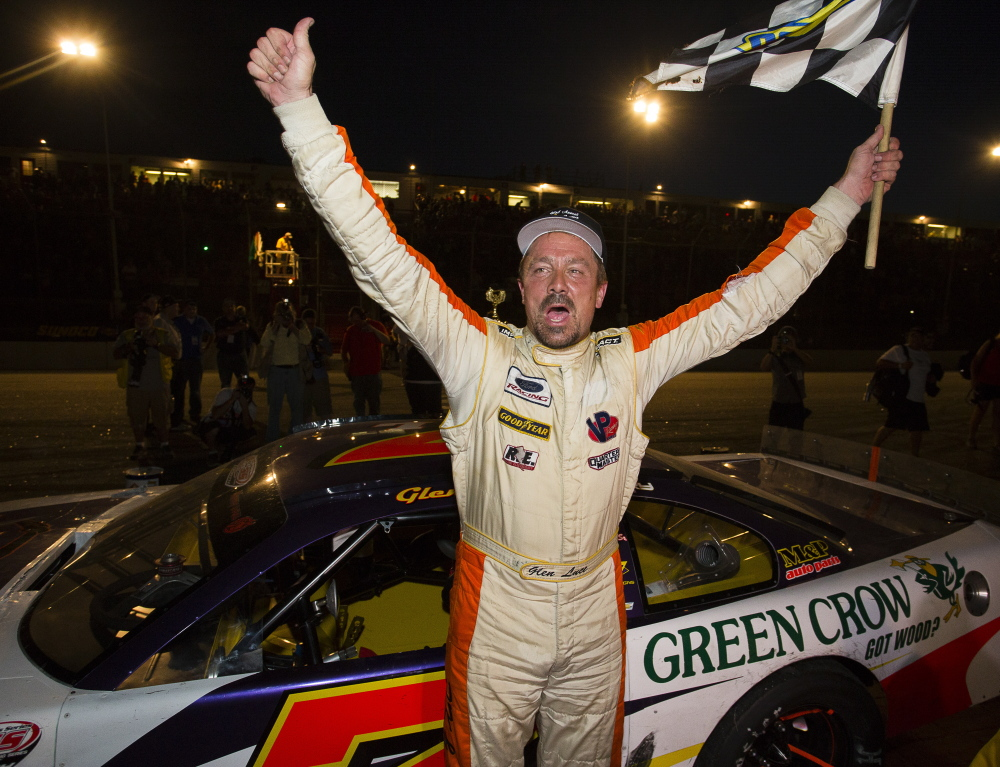 Glen Luce, of Turner, raises the checkered flag after winning the Oxford 250 at Oxford Plains Speedway on Sunday.