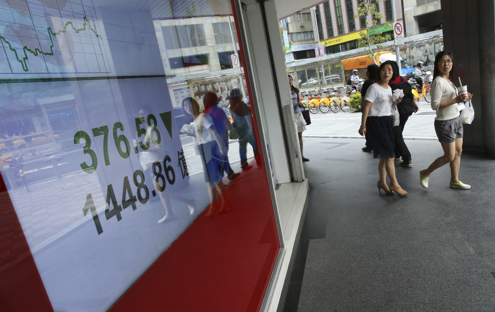 Office workers pass by monitors displaying the Taiwan Stock Exchange in Taipei on Monday. Stocks tumbled across Asia, with China's main index losing more than 8 percent as investors, shaken by the sell-off last week on Wall Street, unloaded shares in practically every sector.