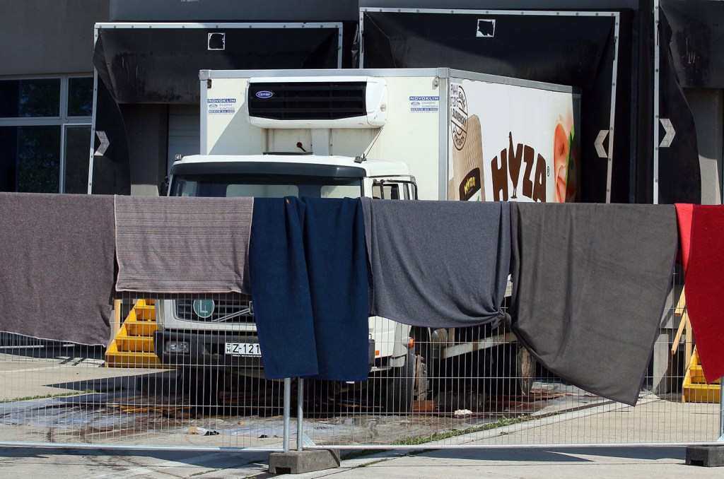 Blankets cover the view on a truck that is investigated at a veterinary border station at the Austrian/Hungarian border in Nickelsdorf, Austria, Friday. The truck was found parked on a main Austrian highway on Thursday with 71 migrants suffocated to death. The Associated Press
