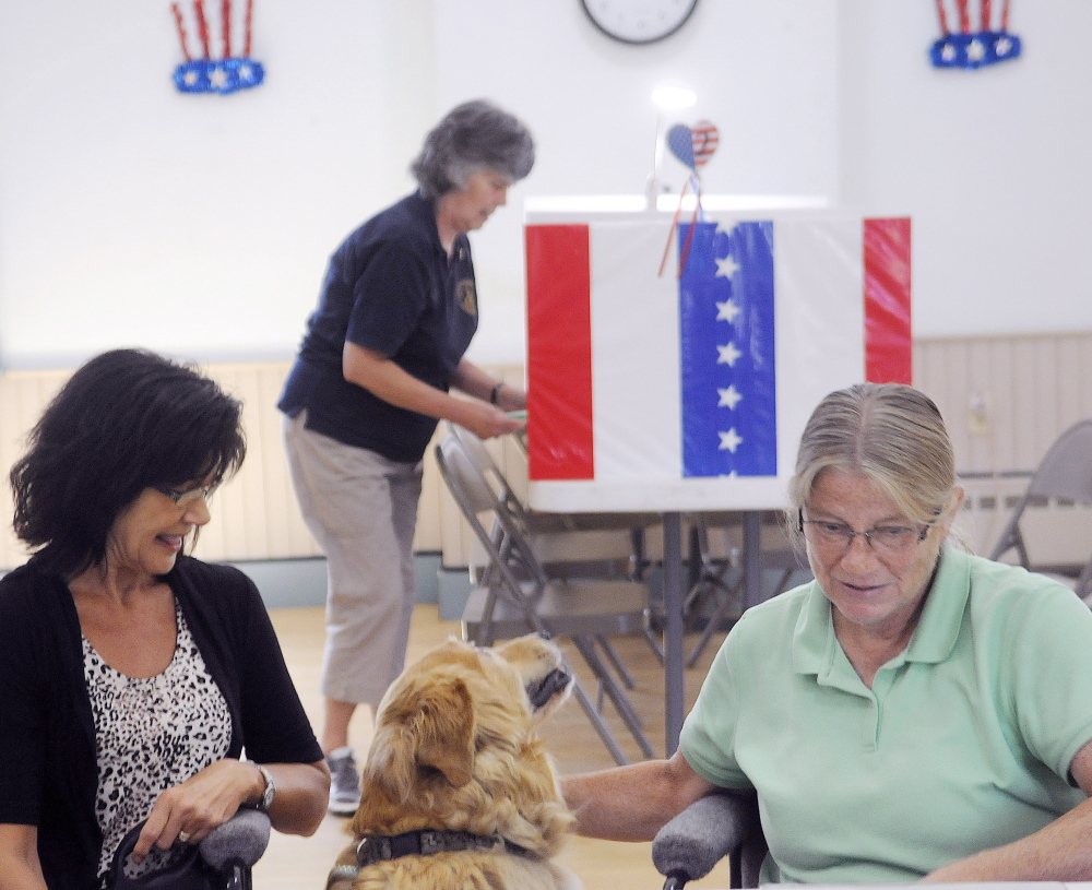 Grace Keene, center, votes Tuesday at the Readfield town hall as her dog, Murphy, waits with clerks Marilyn Palmer, left, and Karen Peterson.