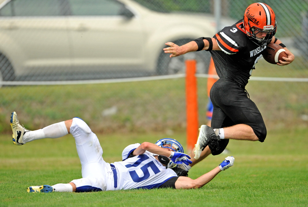 Staff photo by Michael G. Seamans Madison defender Matt Curtis, bottom, tries to wrap up Winslow running back Dylan Hapworth during a game last Sept. 6 in Winslow.