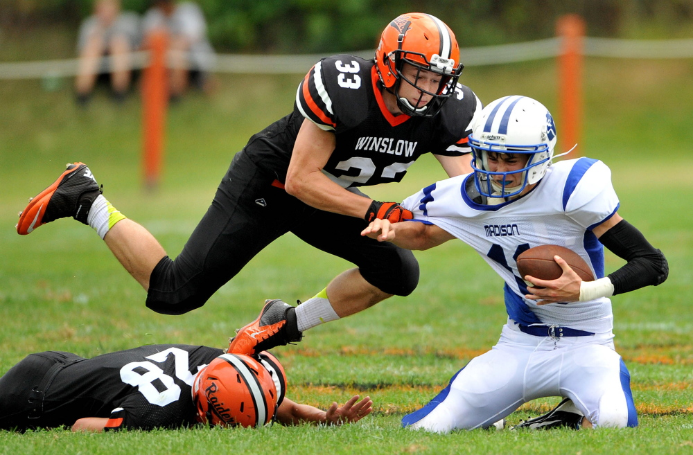 Staff Photo by Michael G. Seamans Winslow defensive linemen Luke Fedette (28) and Ryan Fedette (33) sack Madison quarterback Chase Malloy during an Eastern C game last Sept. 6 at Poulin Field.