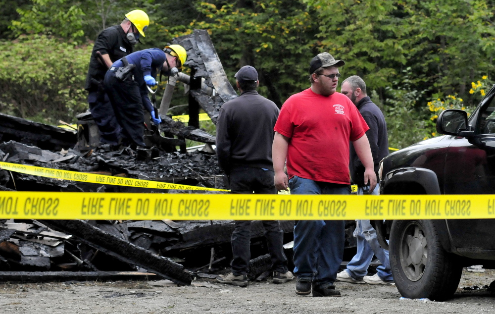 Dylan Ellis, front, walks away from the scene of a fire that destroyed his grandmother's home where he was staying on Maple Lane in Canaan early Sunday. State fire marshal investigators John Wardwell, upper left, and Jeremy Damren look for clues to the cause in the living room area as Canaan Fire chief Troy Bowden, center, and firefighter Ed McGovern watch.