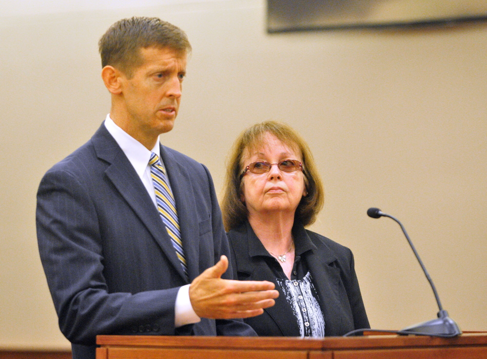 Attorney Walter McKee stands with Claudia Viles as she pleads not guilty plea in an initial appearance on Thursday in Kennebec County criminal court in Augusta. She is charged with 13 counts related to tax fraud at the Anson Town Office.