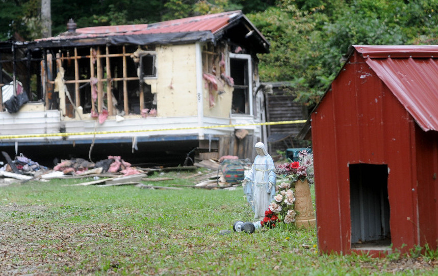 A mobile home at 289 Brown's Corner Road in Canaan was destroyed in fire on Monday and according to neighbors pets were killed by the blaze. This photo shows the charred remains of the home juxtaposed to the dog house and a statue of Mother Mary on Tuesday, Sept. 22, 2015. It is the third fire in that town in three weeks.