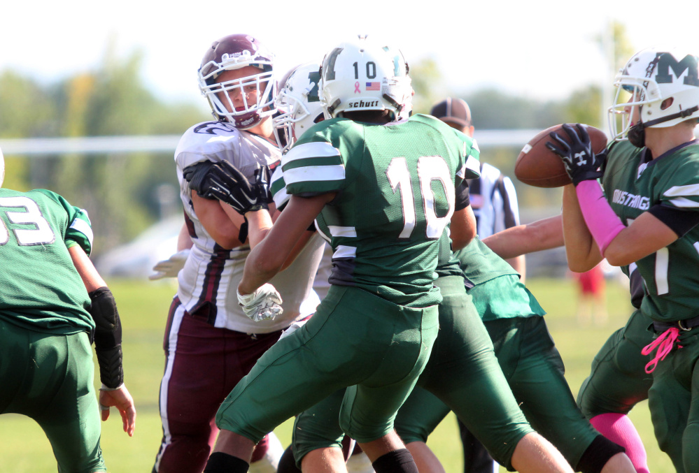 Photo by Jeff Pouland   Maine Central Institute's Curtis McLeod eyes quarterback Rayno Boivin during the third quarter of last Saturday's game against Mount View High School in Thorndike.