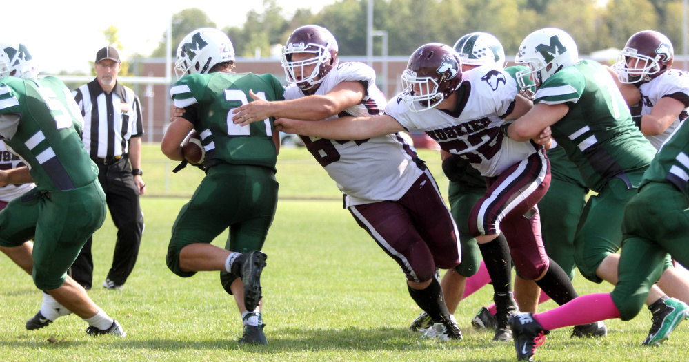 Photo by Jeff Pouland   Maine Central Institute's Curtis McLeod (64) and Mike Steeves (62) reach out to tackle Jack Axsom during the third quarter of last Saturday's game against Mount View High School in Thorndike.