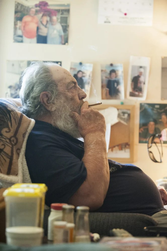 Rockland, Maine--09-01-2015-- Harvey Lembo sits in his living room  in Rockland next to his wheel chair smoking a cigarette on Tuesday. Lembo allegedly shot  Christopher Wildhaber after he broken in and told Lembo he was there to rob him. Lembo has been robbed 5 times in 6 years, until he bought an antique hand gun on Monday.   Kevin Bennett Photo