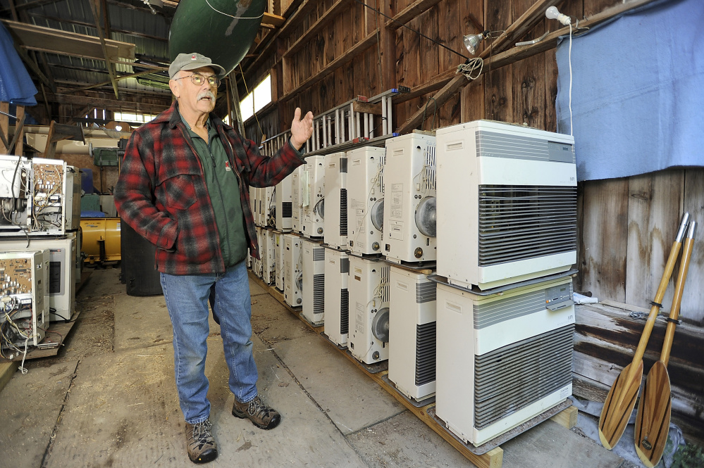 Ken Gaudin, owner of Ken's Monitor & Toyo Sales, stands beside monitor heaters that he will renovate or cannibalize for parts. The demand for the efficient, kerosene-burning Monitor heaters – and for parts to fix them – is great.