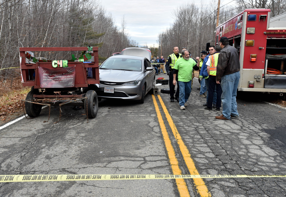 Rescue workers from Waterville fire department and Delta Ambulance tend to multiple victims after a horse-drawn wagon was hit by a car Christmas Day. One of those injured in the crash, Kathy Marciarille, of Rome, died Sunday night.