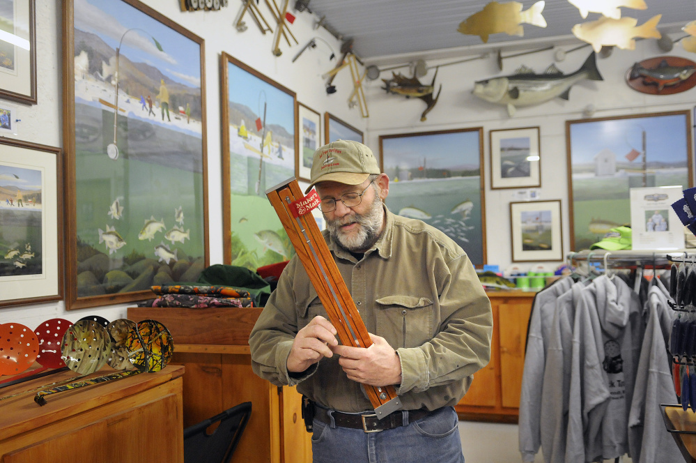 """Jack Traps CEO Timothy Jackson inspects a custom-made ice fishing trap at his retail and manufacturing shop in Monmouth on Monday. The sale of the hand-made ice fishing traps is dependent upon the upon mother nature, he said. """"We're all in her hands,"""" Jackson said."""