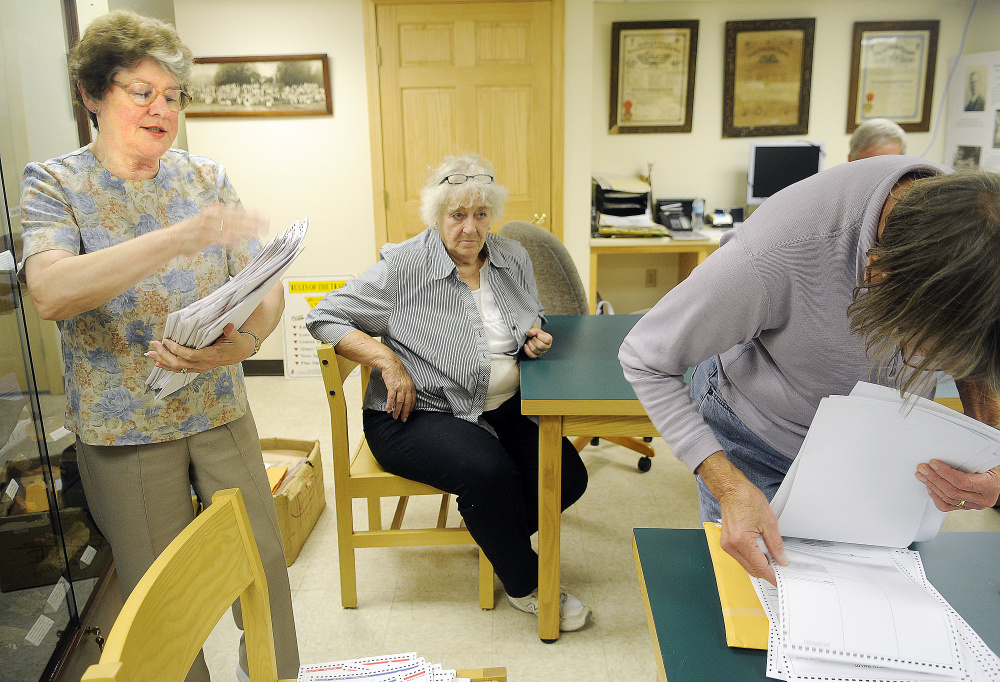 Rayna Leibowitz, left, and ballot clerk Dian White, right, inspect ballots Monday at the Litchfield town hall as Esther Slattery, seated, observes.