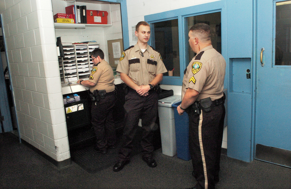 "Thomas College student and Kennebec County Correctional Facility intern Tyler LeClair, center, speaks with Cpl. Sean Cipriano with officer Myra Gagnon behind him at the Augusta jail. LeClair is studying criminal justice and has put some of his ""empathy-based"" education to the test in his summer job."
