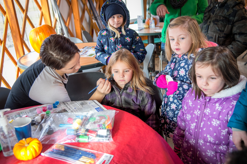 Brenna Rolfe gets a cat painted on her face Saturday by Fall Festival volunteer Cailynn Colby at the Quarry Road Trails recreation area in Waterville.