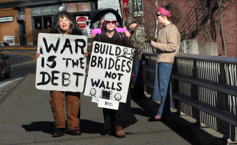 War protesters, from left, Abby Shahn, Lisa Savage and Selene Spivak and others hold signs Sunday on the Margaret Chase Smith bridge in Skowhegan.
