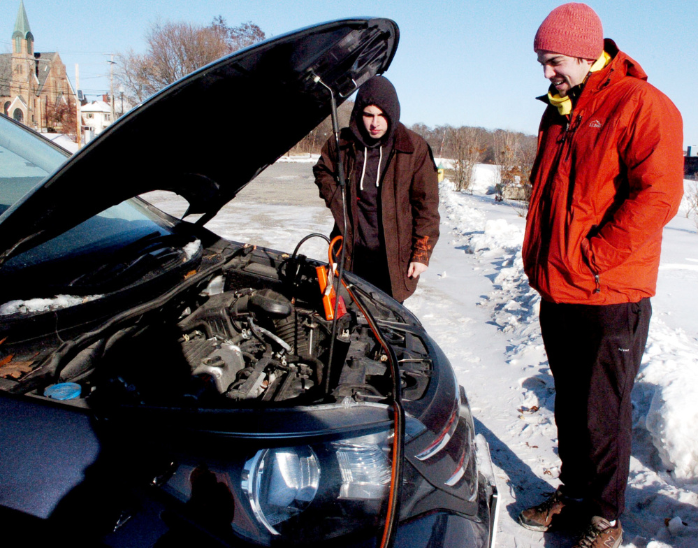 As the temperature falls below zero Friday morning, Colin Finn, left, and Charles Gauvin anxiously wait for the car battery to charge while getting a boost at Head of Falls in Waterville.