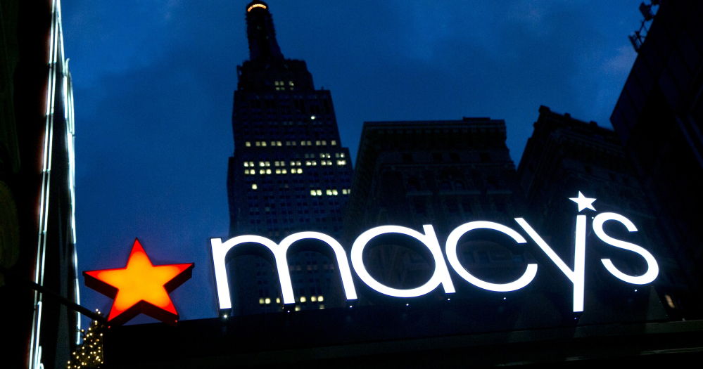 With the Empire State Building in the background, the Macy's logo is illuminated on the front of the flagship department store in New York.