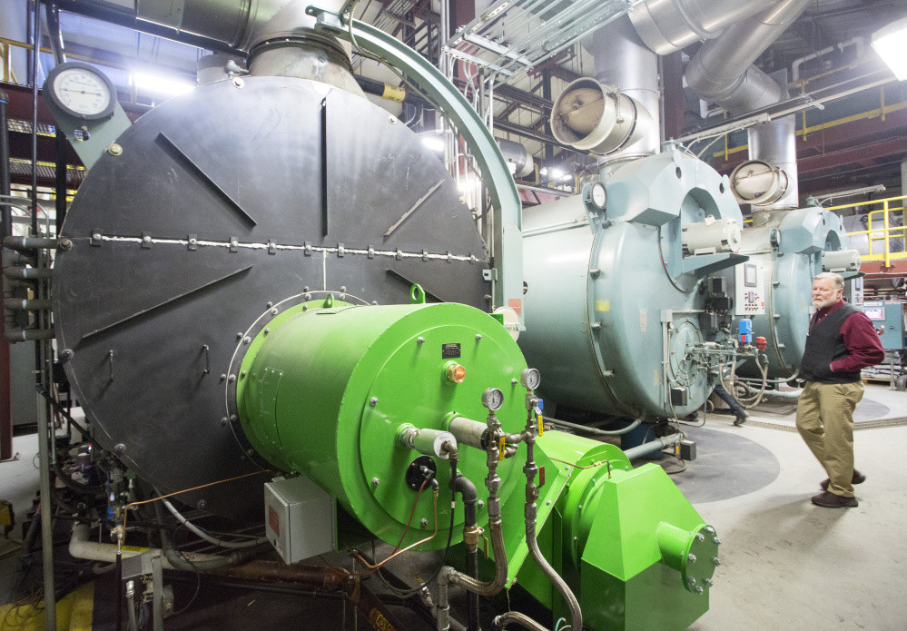 Bates College energy manager John Rasmussen gives a tour of the boiler room housing a new unit, left, that burns wood waste-derived biofuel from Ensyn Corp. The school switched to the new fuel in January to reduce its carbon footprint, and Rasmussen expects the investment to pay for itself within five years.