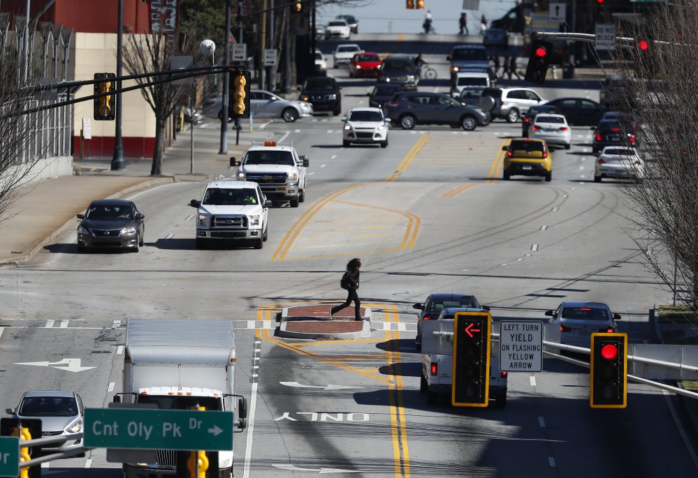 Pedestrians and cars move along a busy section of North Avenue near the Georgia Tech campus in Atlanta. This area might be a proving ground for driverless cars soon.