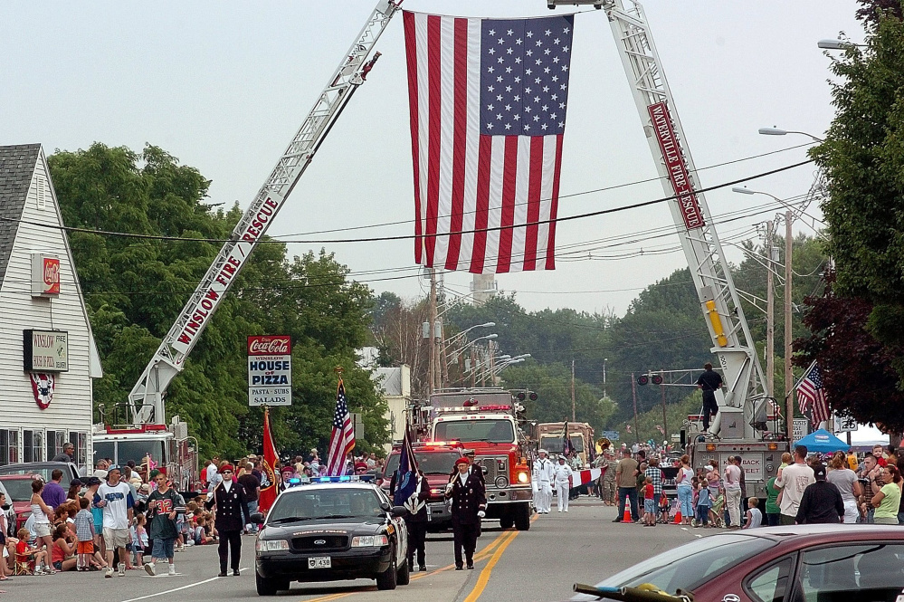 Participants of a previous Winslow Fourth of July parade pass under a huge American flag on Bay Street suspended by ladder trucks from the Winslow and Waterville fire departments. Event organizers aren't sure where the celebration will be held this year, if at all.