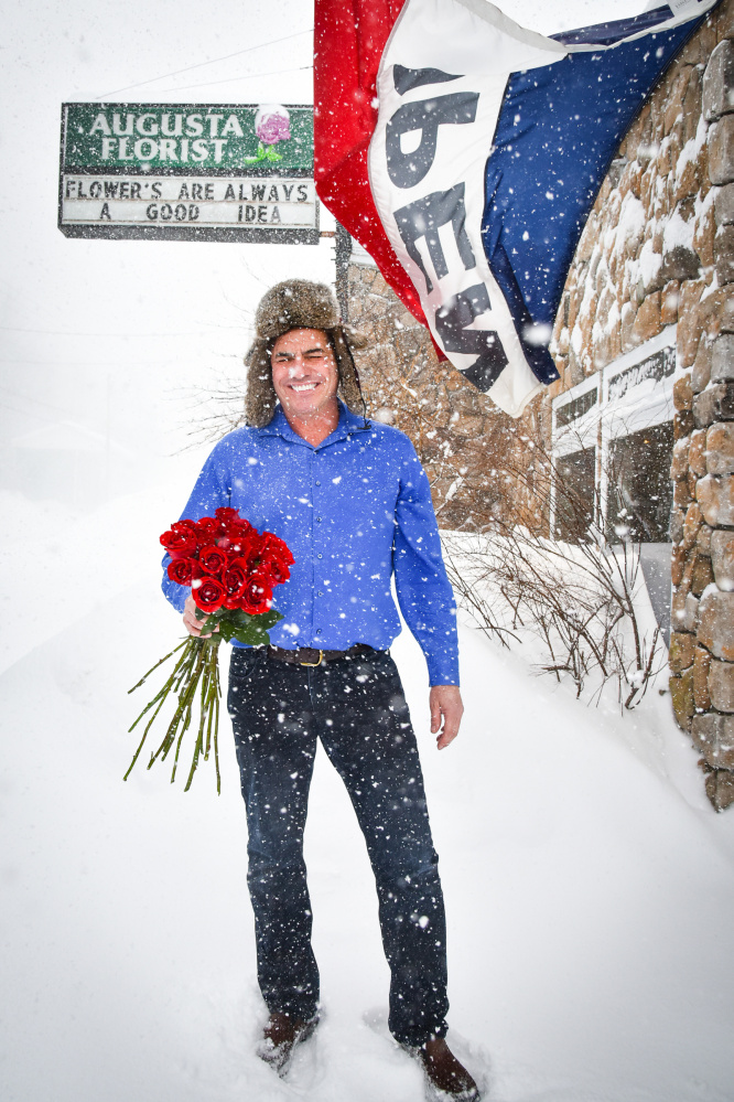 Scott O'Brien, owner of Augusta Florist on Mount Vernon Avenue, holds a bunch of red roses outside his shop on Monday as his work crew gets ready for Valentine's Day.