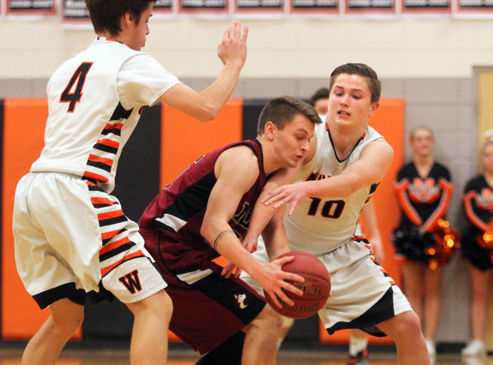 Winslow High School's Michael Wildes, right, tries to steal the ball from Maine Central Institute's Josh Buker as Spencer Miranda looks on during the first half of a Class B North prelim game on Thursday night in Winslow.