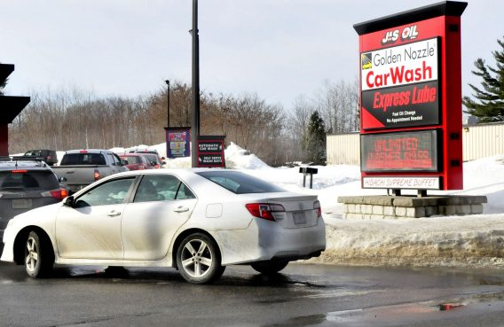 Vehicles are parked in a line on Kennedy Memorial Drive in Waterville to enter the J&S Oil car wash on Wednesday, a day after police warned motorists not to idle along the road while waiting in line for the car wash.