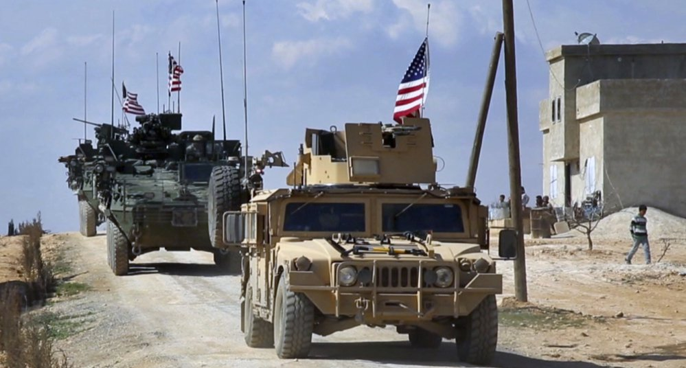U.S. forces patrol on the outskirts of the Syrian town of Manbij. U.S. troops will provide artillery fire in the battle for the Islamic State group's de facto capital, Raqqa.