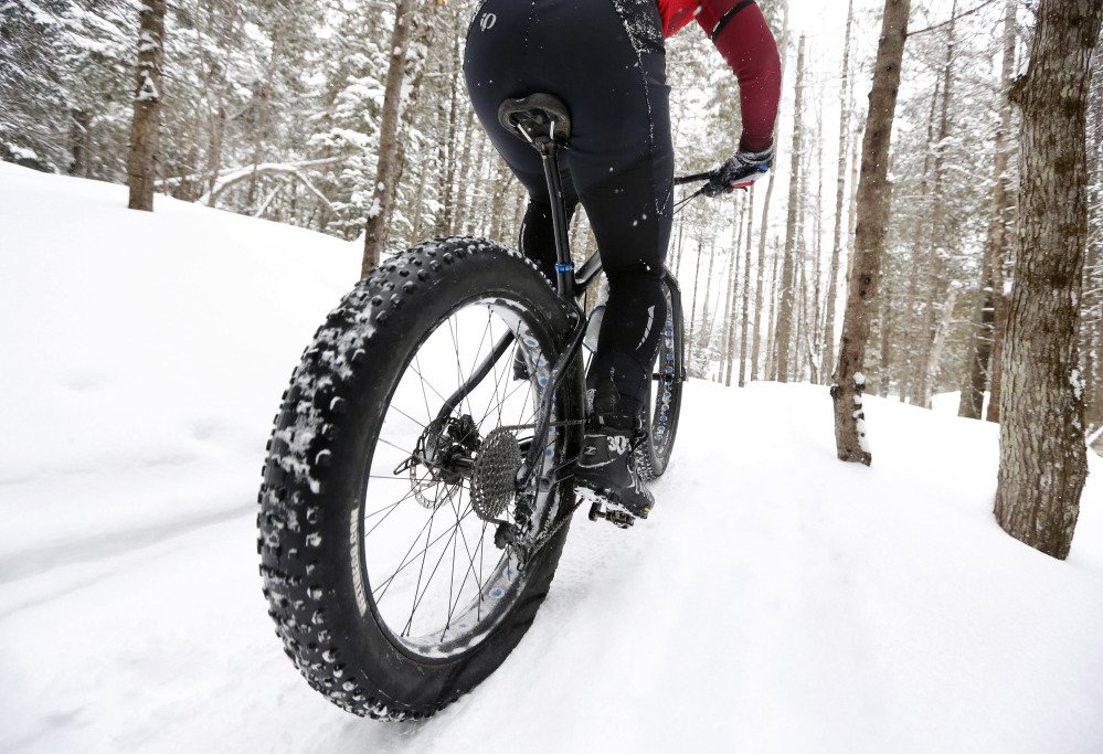 A fat tire bicyclist rides on a cross country ski trail.