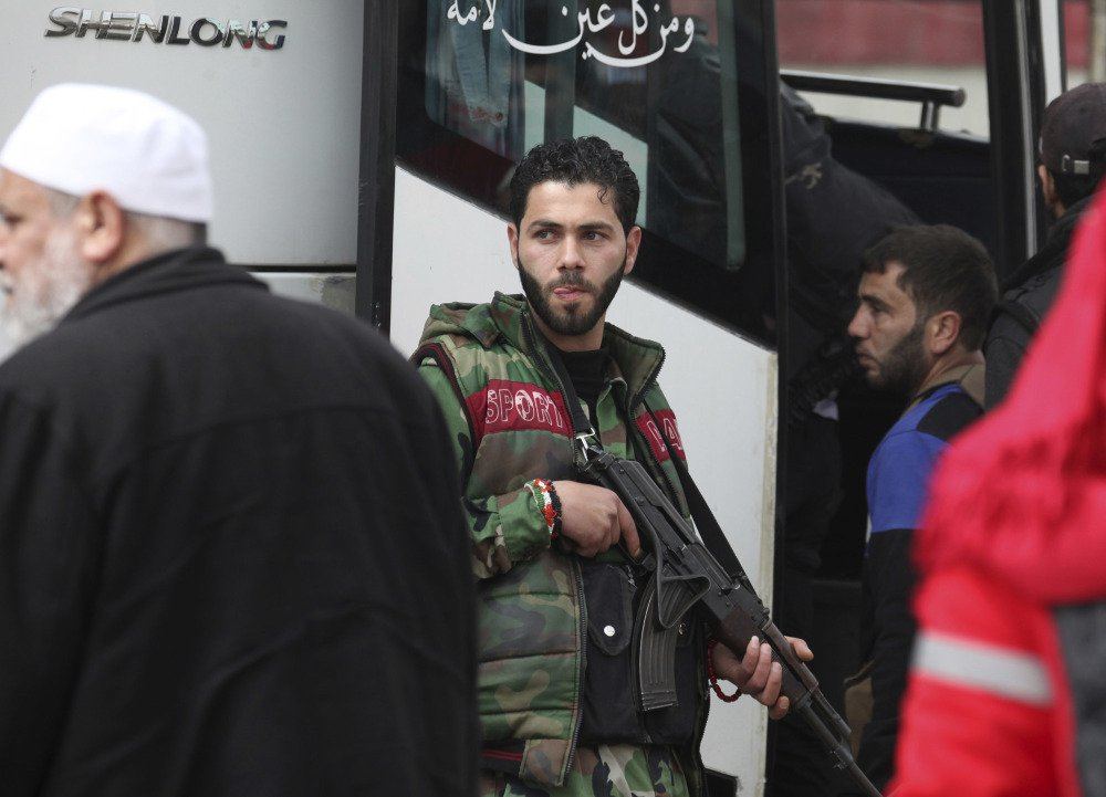 Rebel gunmen carrying their weapons leave the al-Waer neighborhood in Homs, Syria, bound for a town on the Turkish border on Saturday.