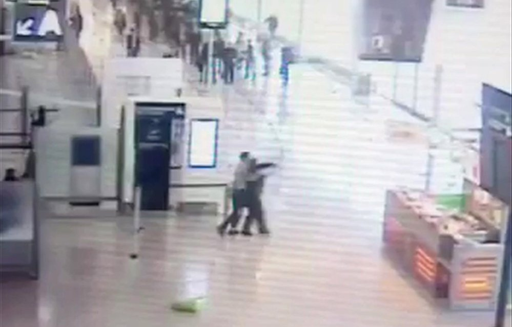 Suspected Islamic extremist Ziyed Ben Belgacem, center left, holds a soldier after grabbing her from behind at Orly Airport in Paris on Saturday. Belgacem was shot dead within three minutes during a standoff with two other soldiers.