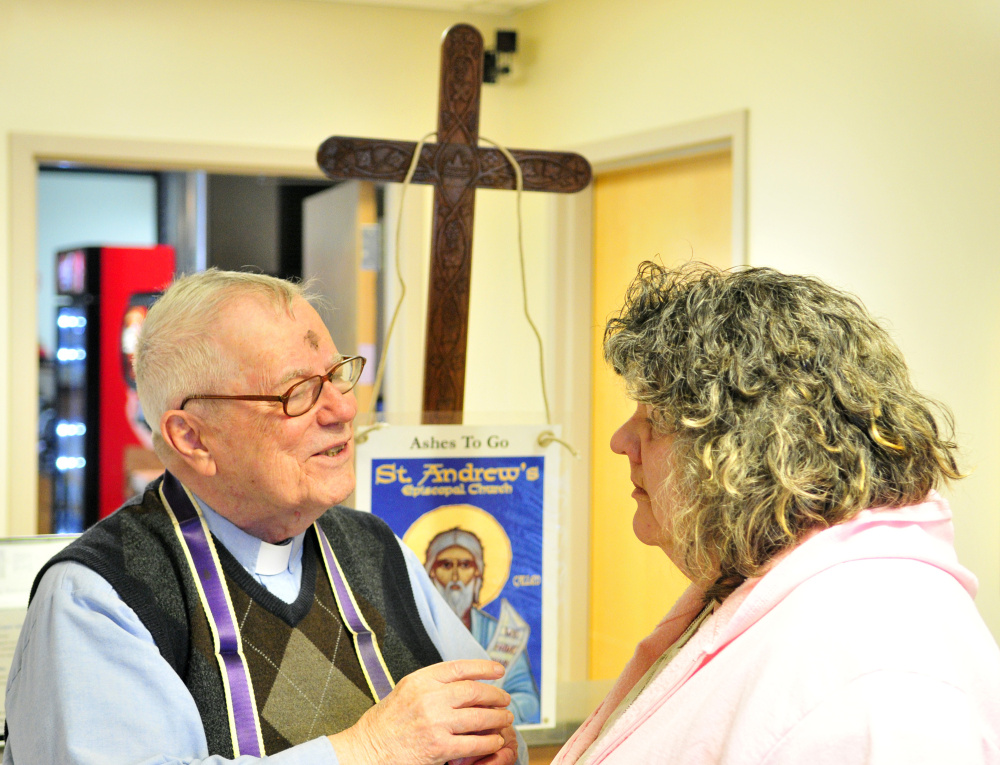The Rev. James Gill chats with Theresa Edwards before marking a cross with ashes on her forehead on Wednesday at the Winthrop Commerce Center.
