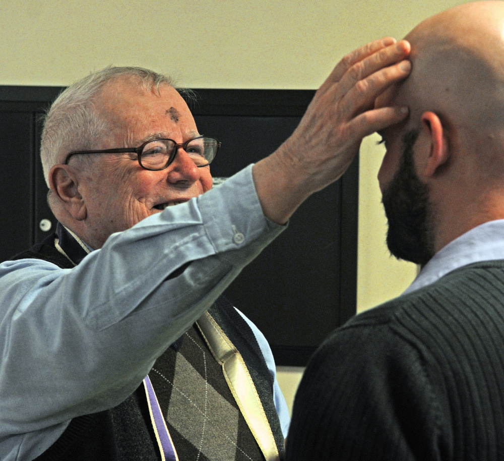 The Rev. James Gill applies ashes to the Stephen Farrington's forehead Wednesday at the Winthrop Commerce Center. Gill was marking people with a small cross in ashes as part the international Ashes To Go program on Ash Wednesday, the beginning of the Christian season of Lent, which leads up to Easter.