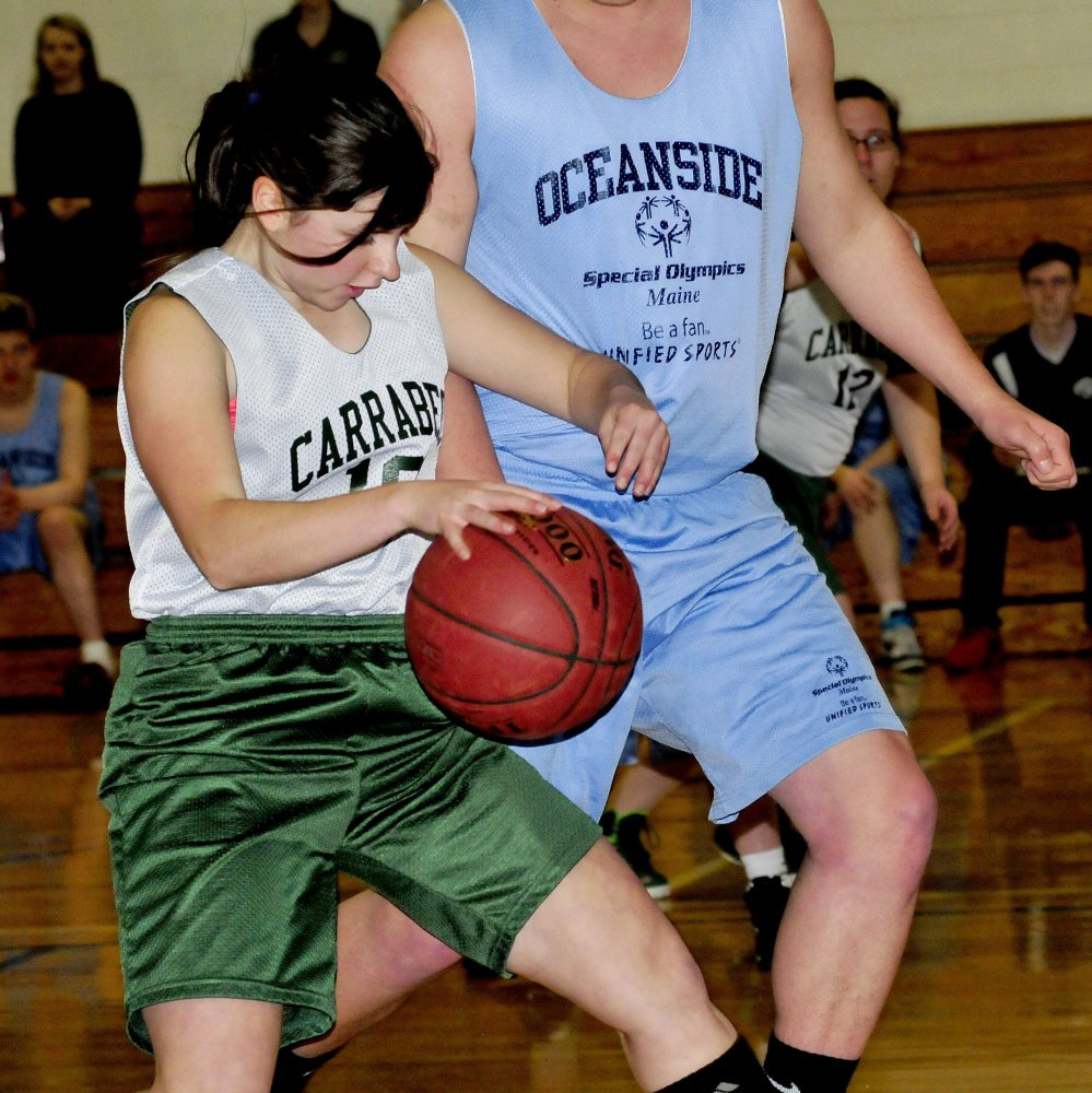 Carrabec/Madison's Kaitlin Dixon tries to get around Oceanside defender  Zachary Gledhill during a unified basketball North quarterfinal Wednesday afternoon in North Anson.