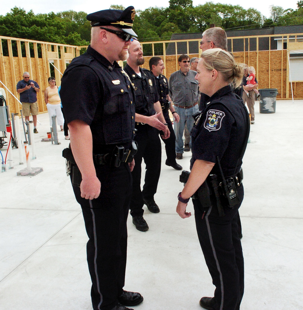 Oakland police Staff Sgt. Peter Tibbetts takes part in an inspection of police officers, including Officer Tanya Allen, during a town swearing-in ceremony May 25, 2016, at the town's new police station. Oakland officers voted Friday to unionize with the Maine Association of Police.