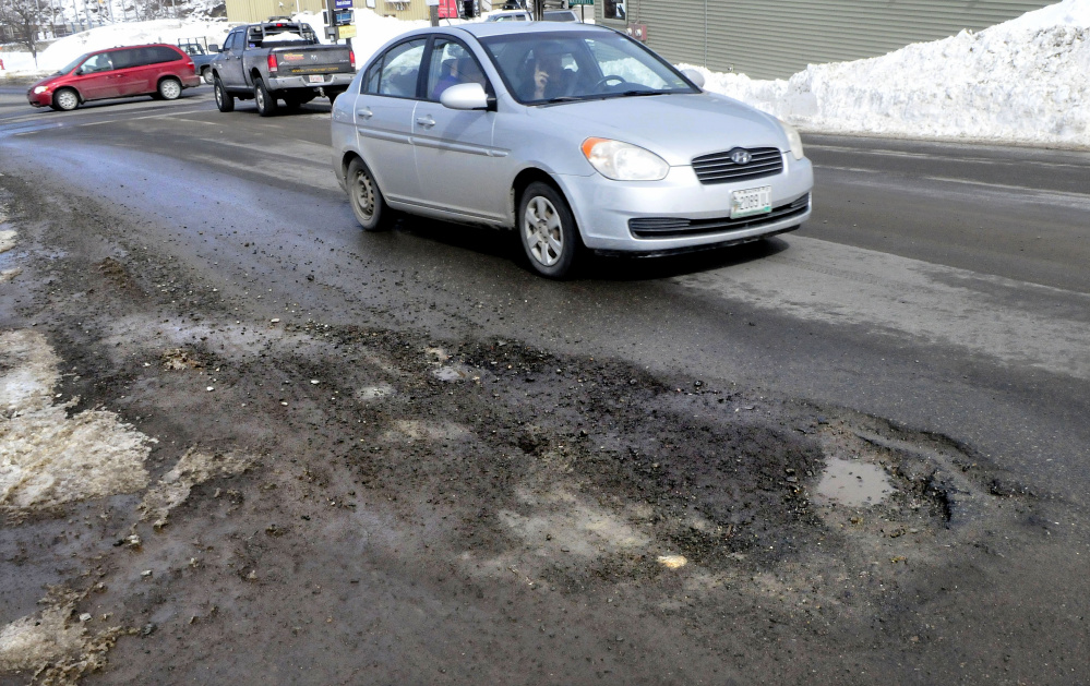 Traffic in Skowhegan tries to avoid running over the potholes on one side of Main Street on Thursday.