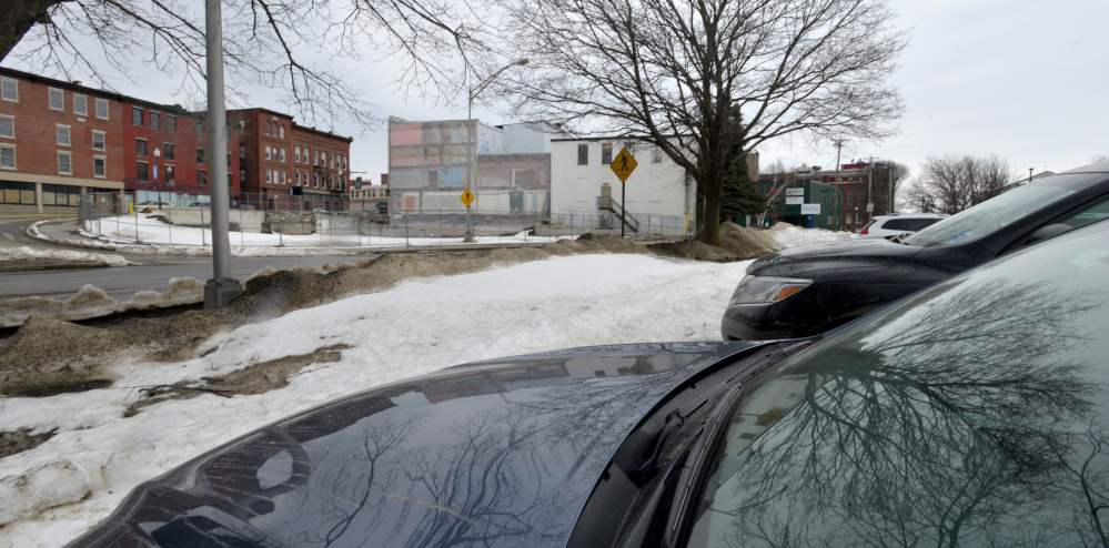 Cars line a city-owned parking lot Tuesday off Front Street, across the street from the site of a planned boutique hotel.