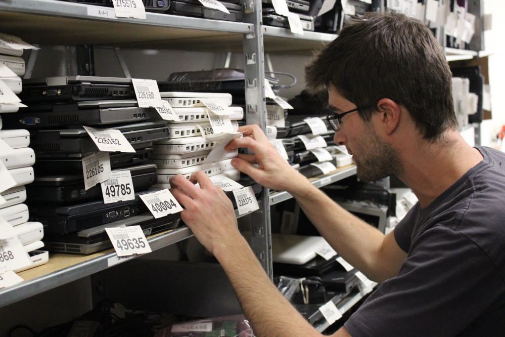 GoodTech employee Eric Landau looks through stacks of laptops in this undated photo from the agency.