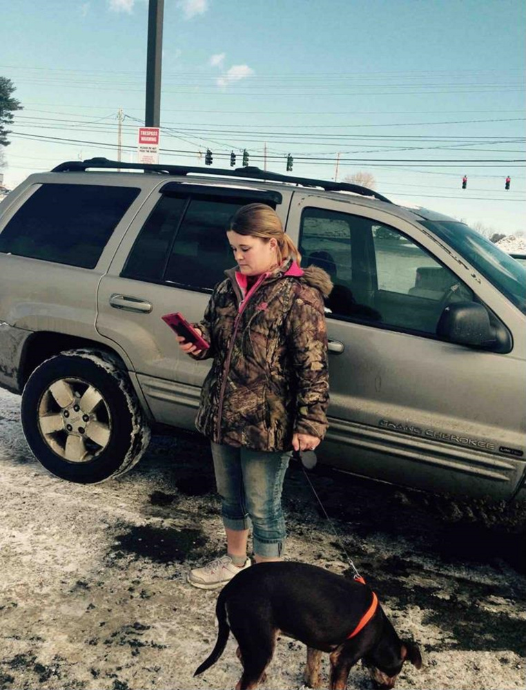 Nicole Bizier, 32, stands by her silver Jeep in the Pizza Hut parking lot with the dog she tried to sell to state animal welfare agents and Skowhegan police on Feb. 2.