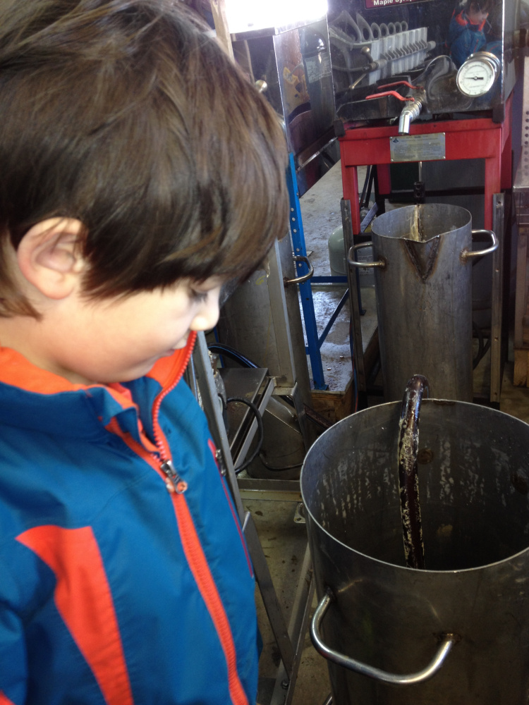Wyatt Pollard, 6, of Benton, peers into a vat of maple syrup that is being pumped into a 15-gallon barrel Sunday under the watchful eye of Kevin Bacon, owner of Bacon Farm Maple Products in Sidney.