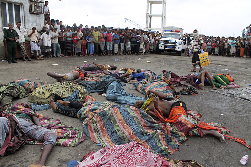 Bodies of Somali migrants, killed in attack by a helicopter while traveling in a boat off the coast of Yemen, lie on the ground at Hodeida, Yemen on Friday.