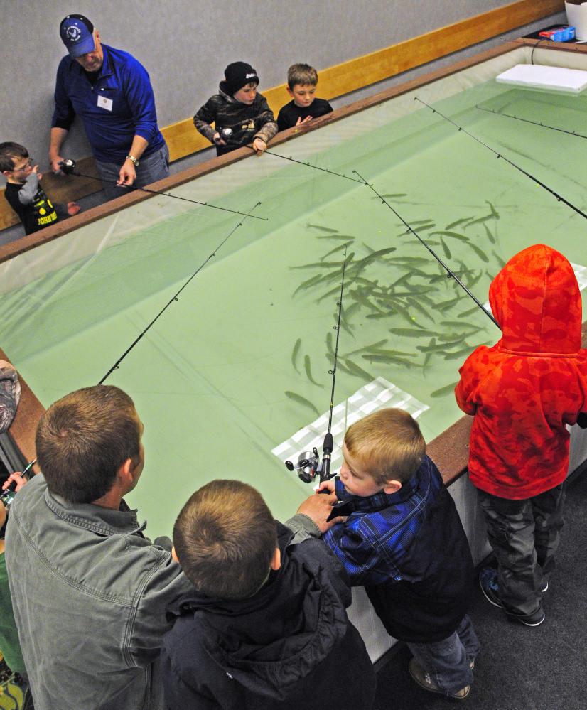 Children try their luck at catching fish Saturday in the Sportsman's Alliance of Maine Kid's Trout Pond during 37th annual State of Maine Sportsman's Show at the Augusta Civic Center.