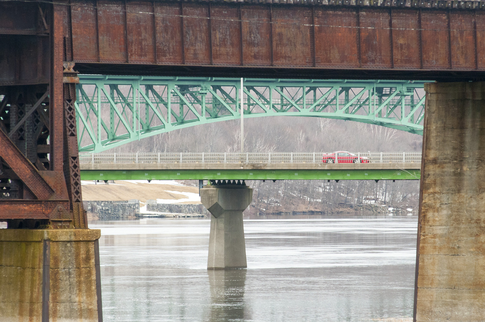 Two bridges over the Kennebec River frame a car going over the Calumet Bridge last week at Old Fort Western in Augusta. Forecasters say minor flooding is expected in Augusta and other areas on Wednesday.