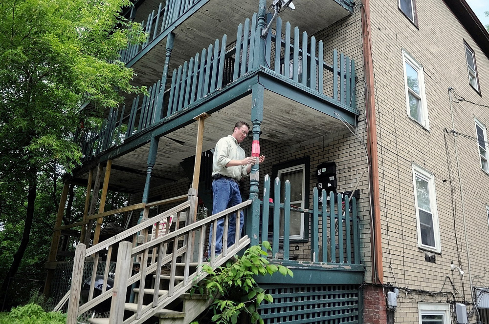 Augusta Code Enforcement Officer Rob Overton tapes a notice indicating the building is unsafe on the deck at 11 State St. in this May 2012 file photo. Tenants in the units were ordered to relocate then, and now city officials might take possession of the property.