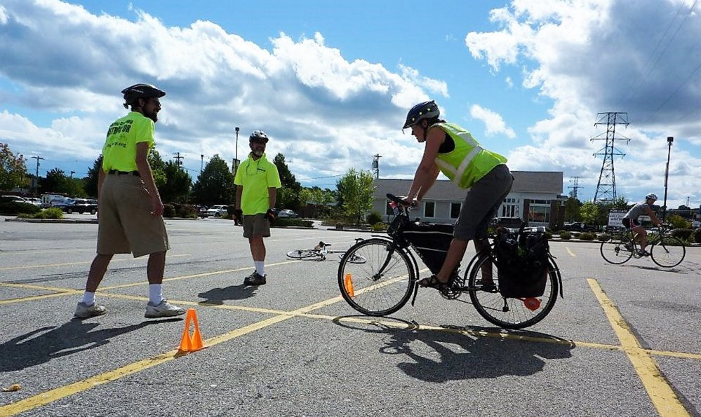 Instructors in a CyclingSavvy class work with a bicyclist on emergency braking. The national program is intended for both novice and experienced bike riders.
