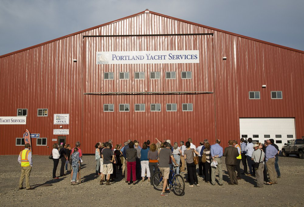 Portland Planning Board members and others get a tour Thursday evening on the waterfront site where a proposed cold storage facility would be built. The nearby Portland Yacht Services building was used to compare what the height of the proposed building might look like.