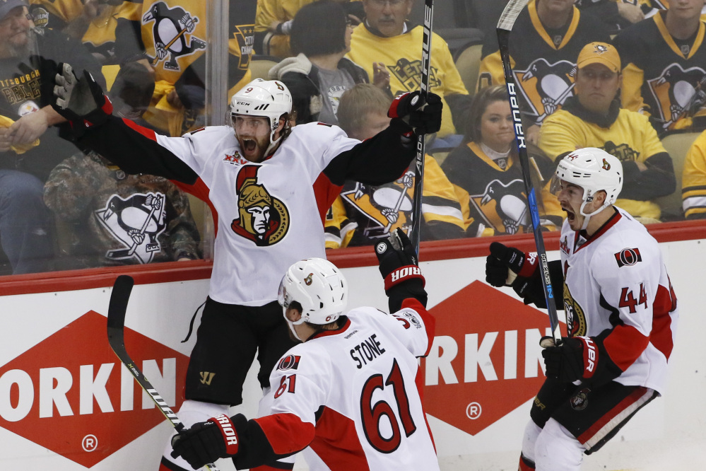 Ottawa Senators forward Bobby Ryan, left, celebrates with teammates Mark Stone (61) and Jean-Gabriel Pageau (44) after scoring the game-winning goal against the Pittsburgh Penguins in overtime of Game 1 of the Eastern Conference final.