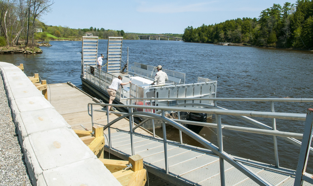 Swan Island staffers push the ferry off from the new dock Wednesday on the shore of Kennebec River in Richmond.