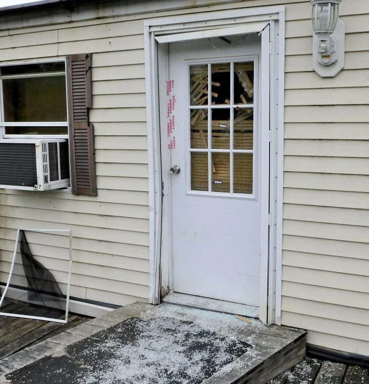 Glass from a shattered window in a door that is sealed with police evidence tape is seen at the front entrance to a mobile home at 1003 Oakland Road in Belgrade on Monday. Homeowner Roger Bubar died in a police officer-involved shooting on May 20 and his son Scott Bubar was wounded.