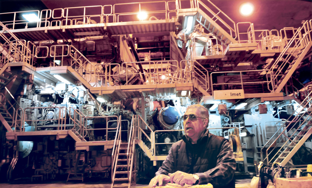 Jaime Broce of Somerset Acquisition LLC and current manager of the former Madison Paper Industries mill stands April 20, 2017, in front of the Number 3 paper making machine that is being sold via private negotiation while other mill assets will be sold at auction beginning June 13.